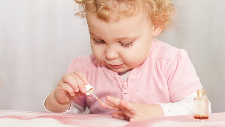 Little girl putting on nail polish