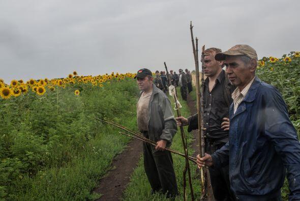 Rebeldes prorrusos y habitantes de la zona peinan el área del suceso.