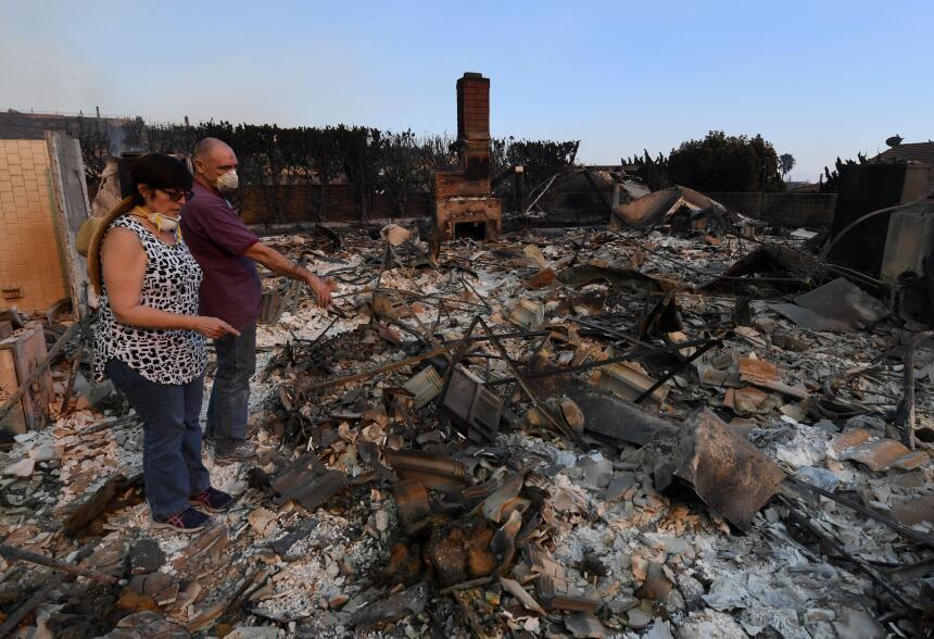 John y Julie Wilson observan los restos de su hogar incendiado después d...