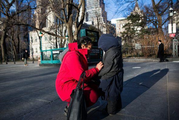 Una mujer abriga a su niño en su camino a la escuela  en Nueva York, Est...