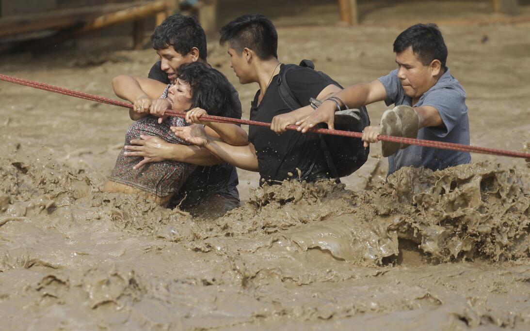 Un grupo de personas, atrapados en las aguas de las inundaciones, se afe...