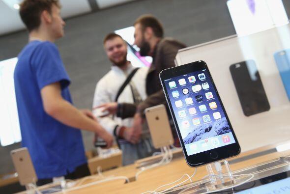 Los compradores platican con un asistente de ventas mientras el nuevo iP...