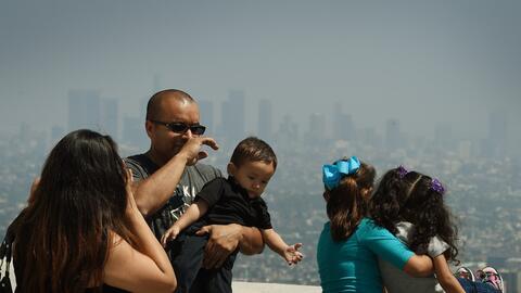 Turistas se asoman desde el Observatorio de Griffith a la contaminada cu...