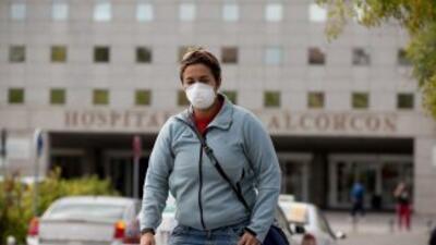 Una mujer lleva puesta una máscara quirúrgica luego de abandonar el hosp...