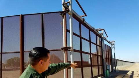 Border Patrol agent Fidel Cabrera points to the triple fence along the Y...