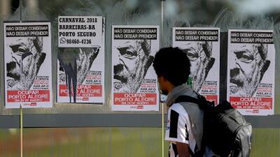 Un transeúnte mira los afiches en apoyo al expresidente Lula da S...