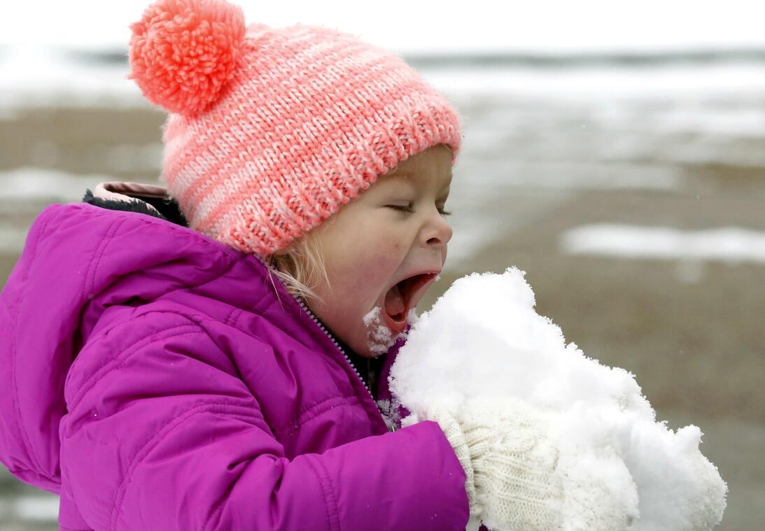 Emmaline Dendinger enjoys a hearty bite of snow in her mid-Jackson, Miss...