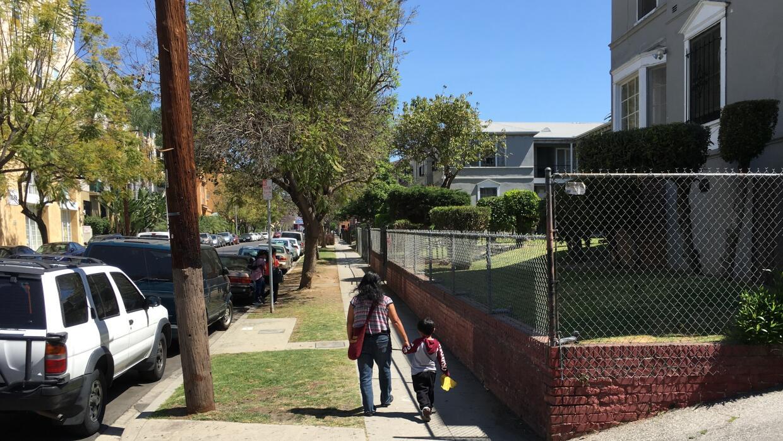 Una mujer camina con su hijo en el barrio angelino Rampart, donde se fun...