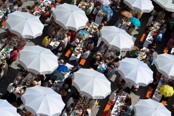 Las personas comparten sus alimentos bajo los paraguas en el Festival de...