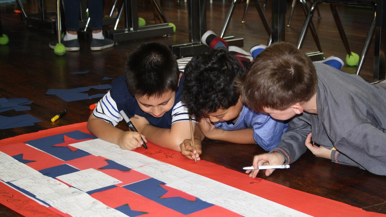 Tres estudiantes colaboran en un proyecto en la Escuela Bilingüe Oyster-...