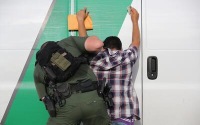 Un agente de la Patrulla Fronteriza registra a un inmigrante en un punto...