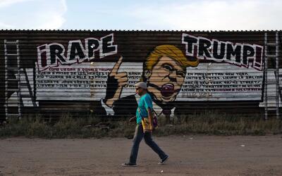 Un hombre camina por delante de la frontera entre México y EEUU.