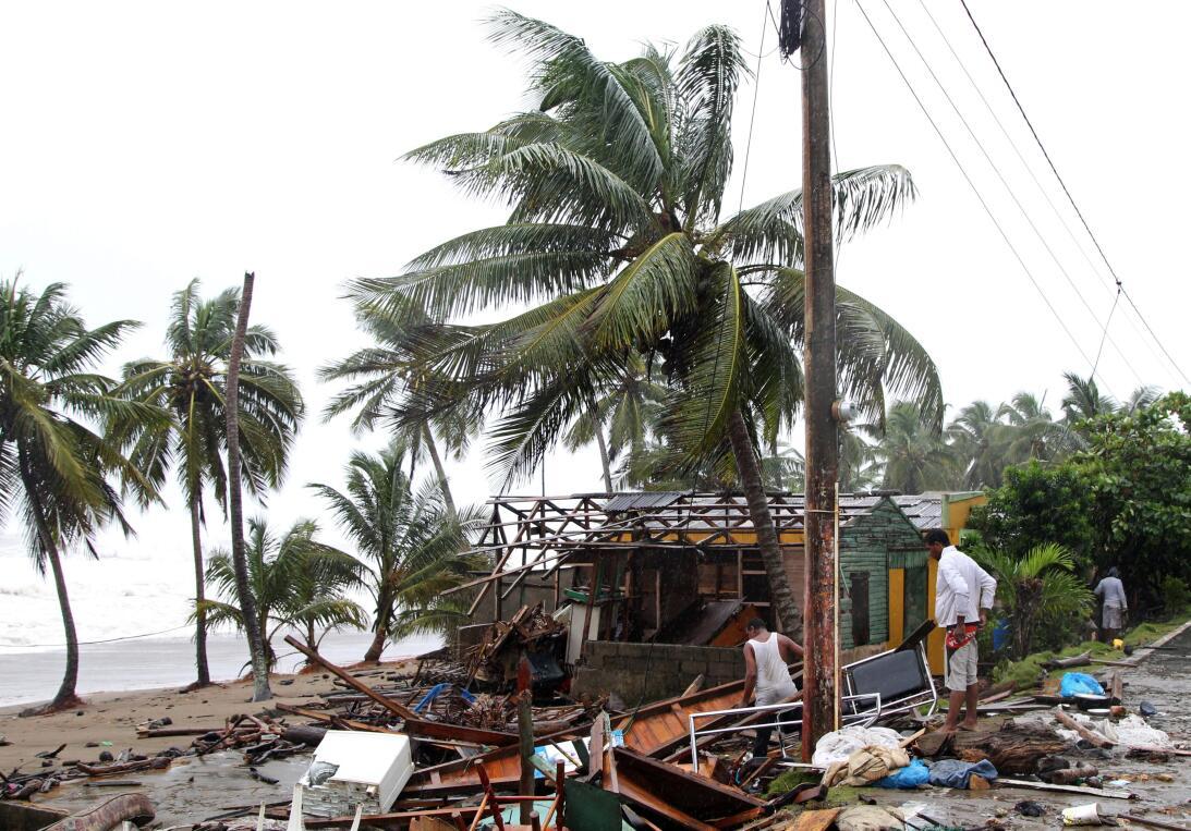 Un grupo de gente mira lo que queda de sus hogares en Nagua, República D...