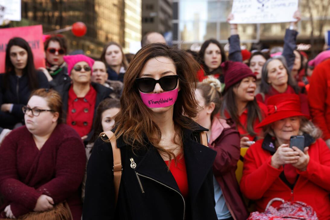 A woman with tape over her mouth takes part in a 'Day Without a Woma...