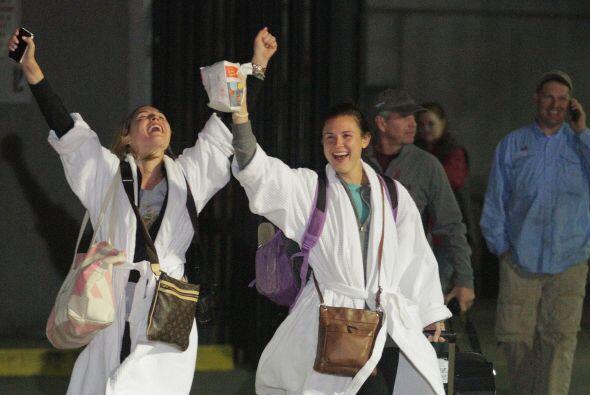 La pasajera Kendall Jenkins, a la izquierda, y su amiga, levantan las ma...