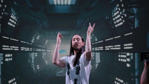 DJ Steve Aoki mixes behind his booth at the Dim Mak Collection SS18 even...