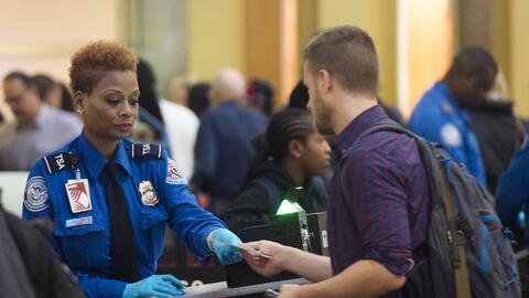 Un pasajero muestra su identificación a un agente de la TSA en un...