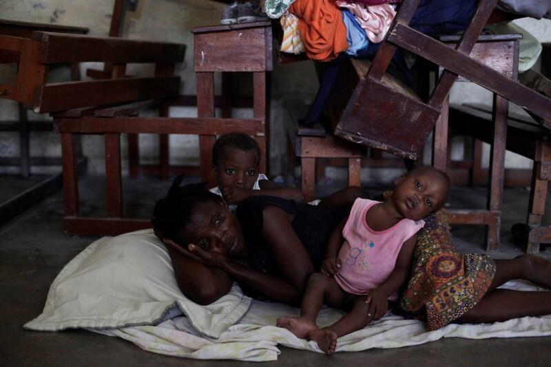 A woman with two of her children rest on the floor at the shelter set up...
