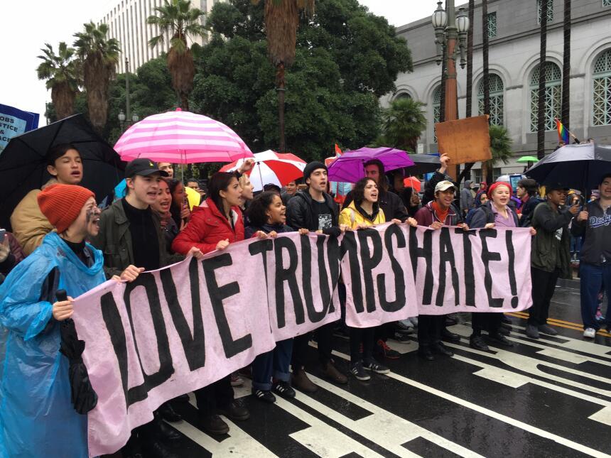 Un grupo de jóvenes de distintas etnias sostiene una manta con el lema:...