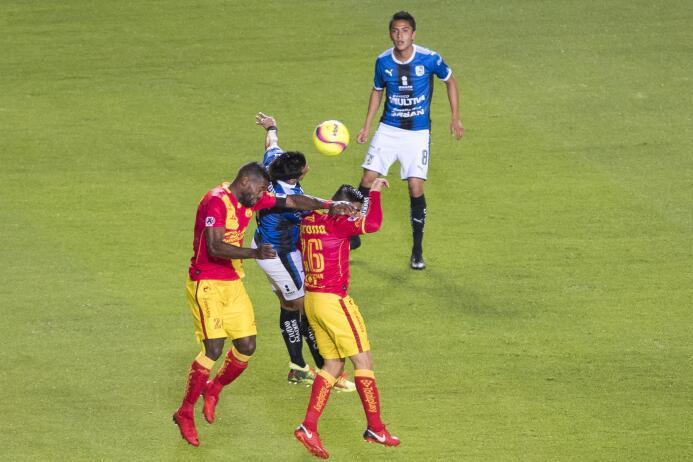 Jugador del Querétaro se disputa un balón en la media cancha ante la dob...