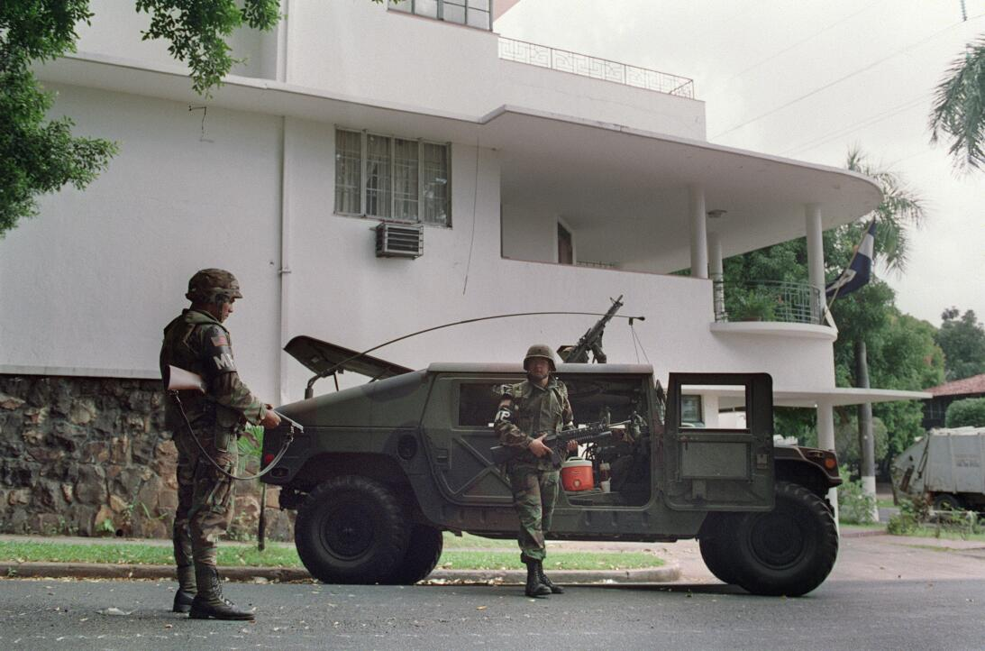 US soldiers stand guard outside the Vatican embassy in Panama City where...