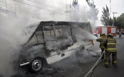Los bomberos trabajan para extinguir un autobús en llamas luego d...