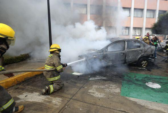 Bomberos tratan de extinguir el fuego en los vehículos incendiados duran...