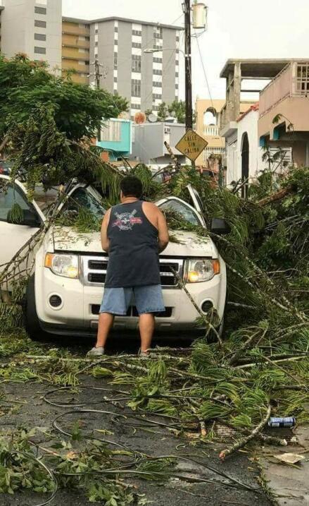 Un hombre remiueve escombros de un auto, en San Juan de Puerto Rico.
