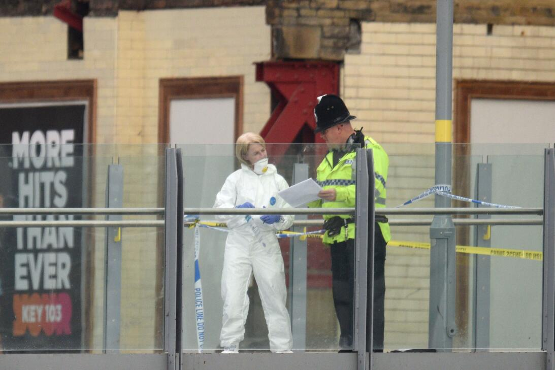 TOPSHOT - A forensic officer (L) collects evidence on a walkway between...