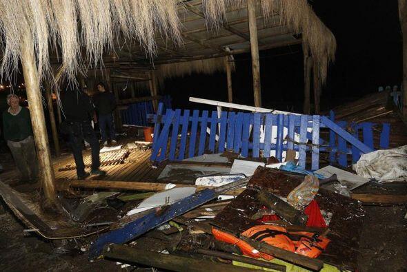 Un bombero chileno pasa al lado de varios destrozos causados una ola des...