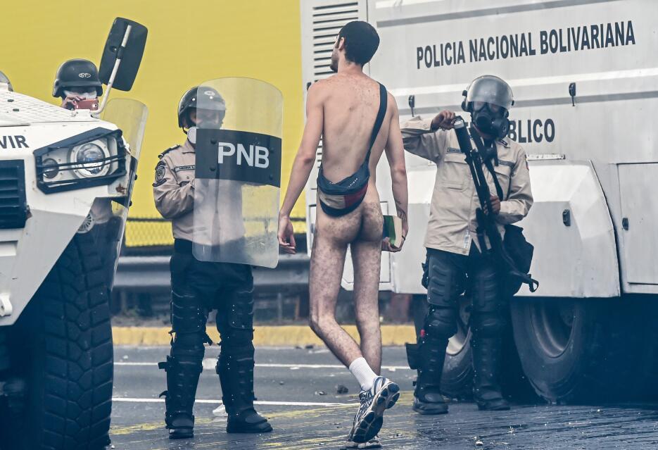 Un joven camina desnudo y con un libro en la mano frente a un grupo de p...