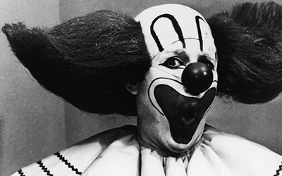 Promotional portrait of Bozo the Clown holding boxes of Bozo Express Baz...