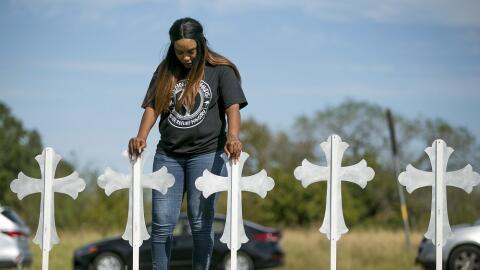 Una mujer reza frente a las 26 cruces levantadas en memoria de las v&iac...