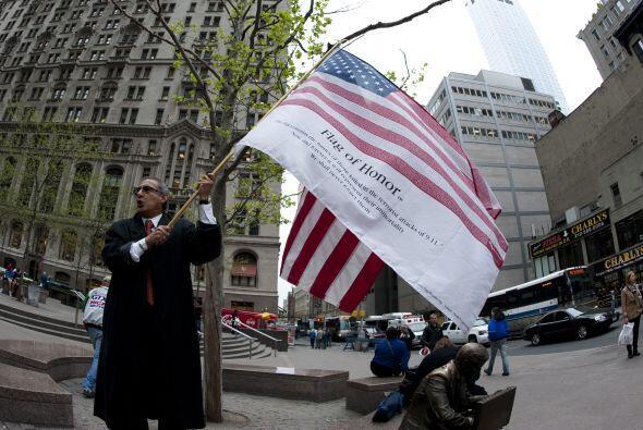 Un hombre ondea la bandera de su país y celebra la muerte del hombre más...