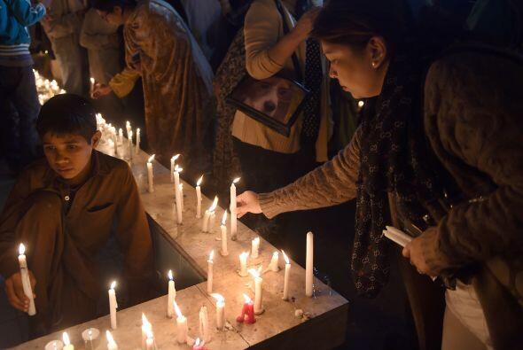 Cientos de personas, entre ellos niños, prendieron velas en una vigilia...