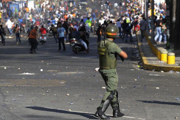 Un soldado apunta a un grupo de manifestantes.