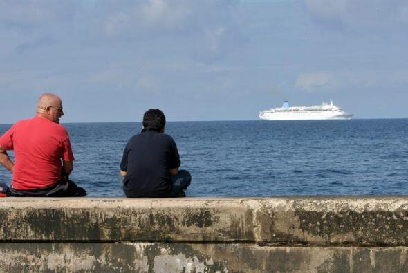 Dos hombres observan un crucero que cruza frente al malecón.