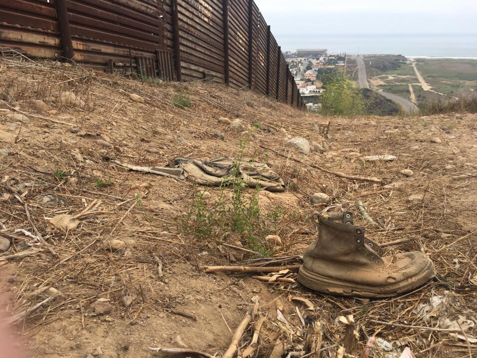 Una bota vieja cerca de la valla fronteriza que concluye en el Oc&eacute...