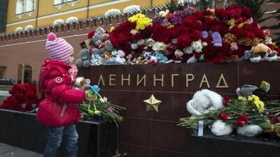 Una niña frente a un monumento en Moscú donde se recuerda a las víctimas.