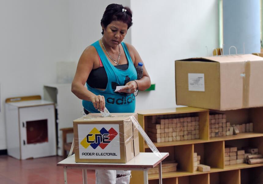 Una mujer vota en Caracas durante la elección parlamentaria de este domi...
