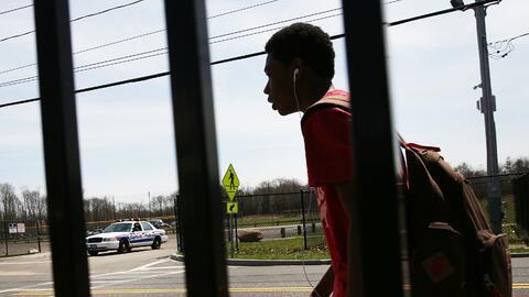 Un adolescente camina frente a un parque en el área de Central Islip, Lo...