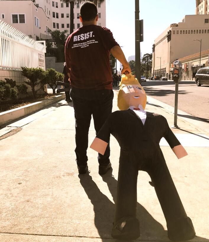 Manifestante en marcha de resistencia contra Donald Trump arrastra una p...