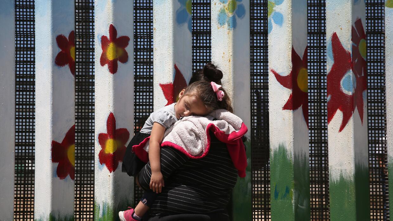 Una mujer hablar con sus familiares al otro lado de la frontera, en Tijuana