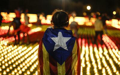 Una voluntaria lleva la bandera independentista catalana en la espalda e...