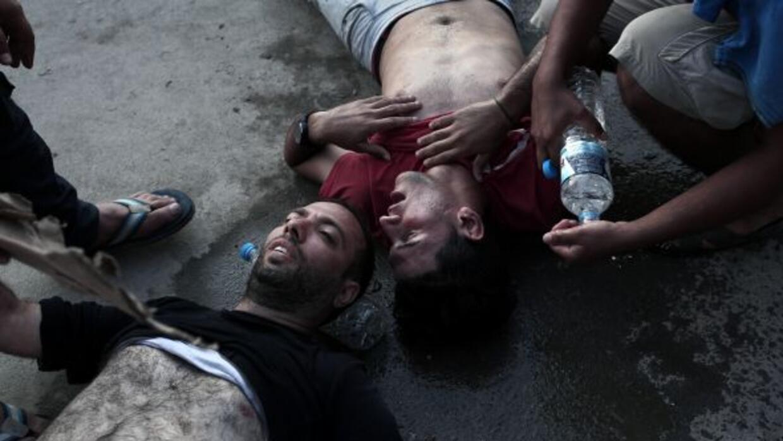 Hombres colapsando antes de ser registrados por la policía en la isla gr...