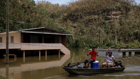 Residentes se mueven en un bote cerca del lago Guajataca.
