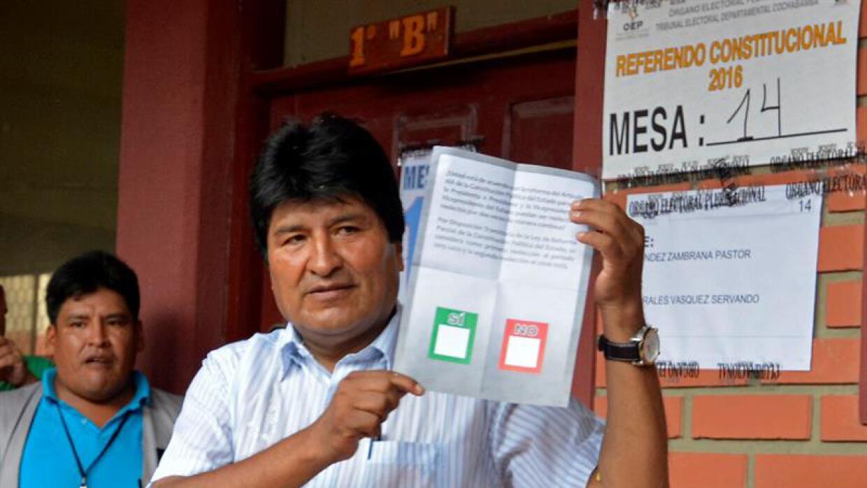 Evo Morales recibe su papeleta para votar en el referendo.