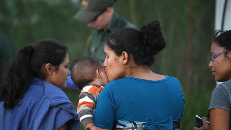 Mujer inmigrante con su hijo en brazos.
