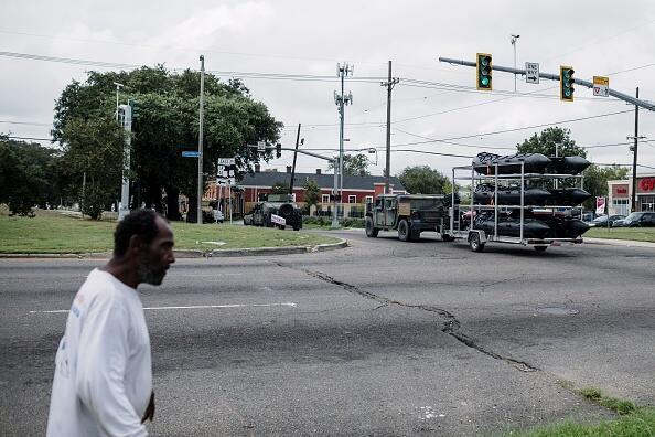 Vecinos de Nueva Orleans ven pasar a los militares con los botes que ayu...
