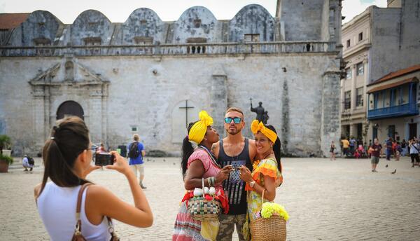 Un turista estadounidense posa para una instantánea entre dos cubanos ve...